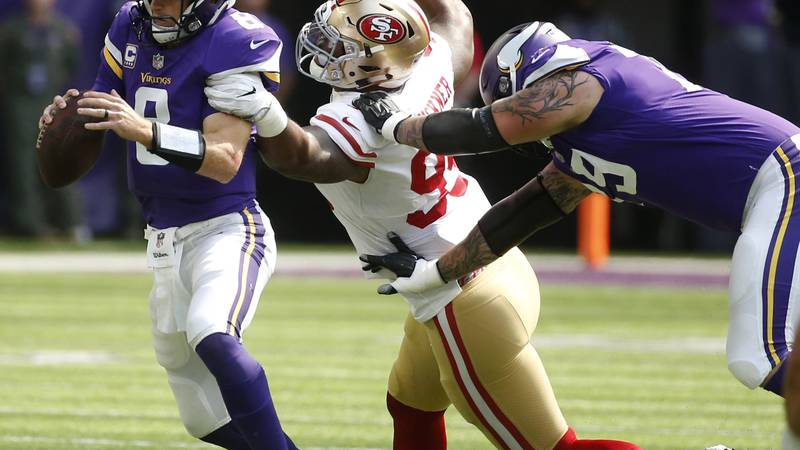 Minnesota Vikings quarterback Kirk Cousins, left, is sacked by San Francisco 49ers defensive...