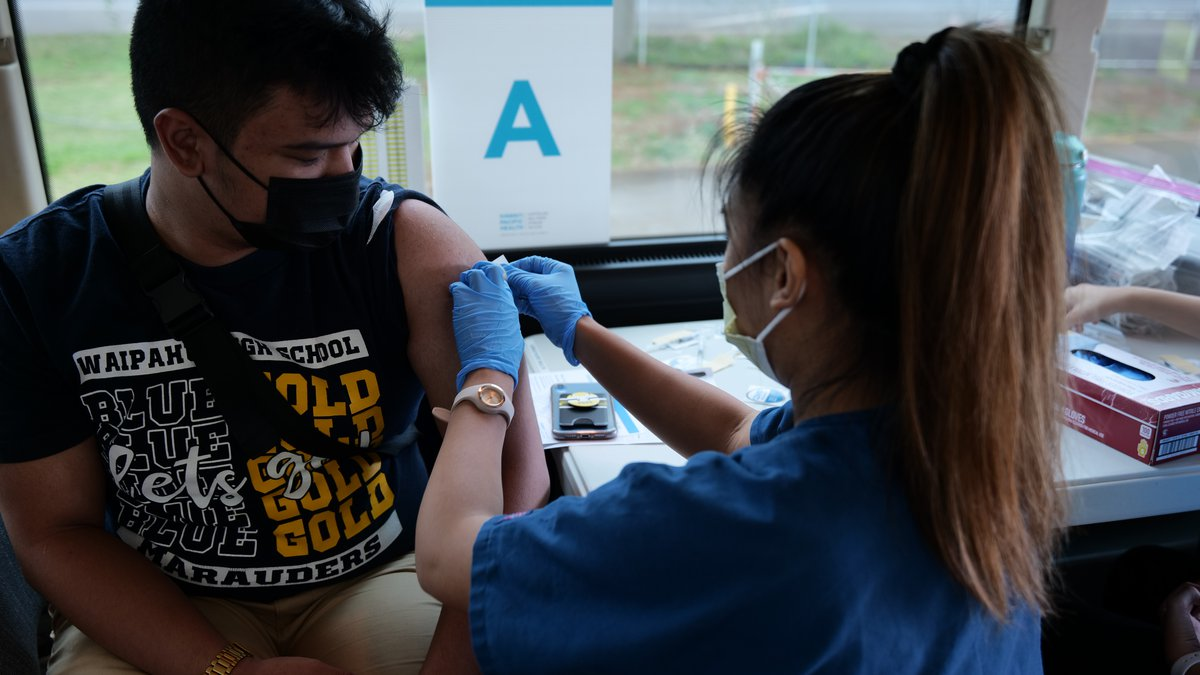 A high school student receives the COVID vaccine at the Waipahu High School clinic.