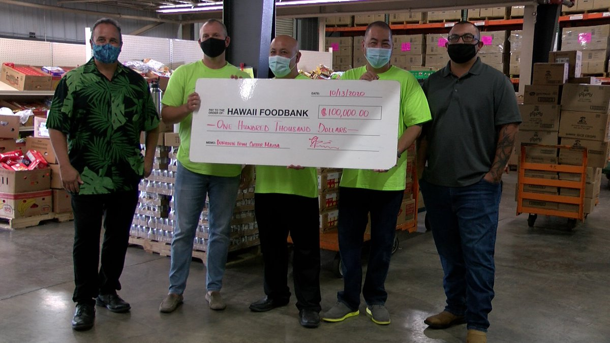 Ron Mizutani, the president of the Hawaii Foodbank, is presented with a $100,000 donation by...