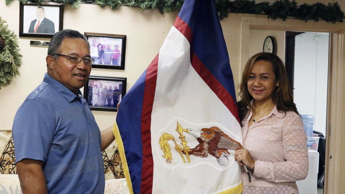 In this Jan. 10, 2020 photo, Filipo Ilaoa, left, and Bonnelley Pa'uulu pose with the flag of...
