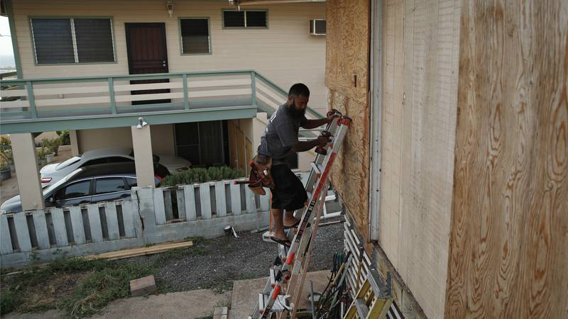 Kaipo Popa secures plywood to protect windows on a home in preparation for Hurricane Lane,...