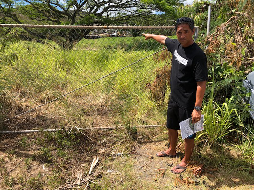 Alika Ferreira points to the 4.9-acre site next to his home that developer Lacus LLC wants to...