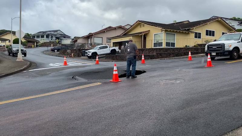 A BWS worker examines the sinkhole that opened up in Aiea Sunday.