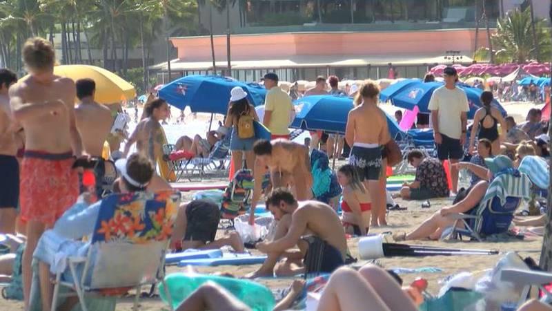 Visitors pack beaches in Waikiki.