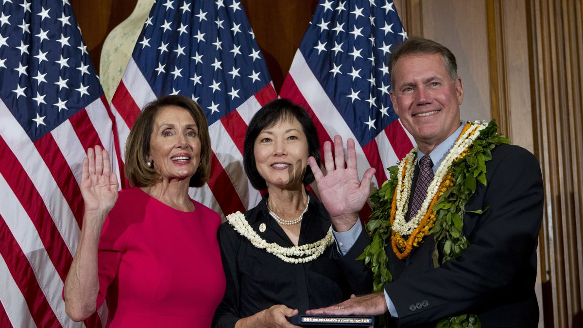 House Speaker Nancy Pelosi of Calif., administers the House oath of office to Rep. Ed Case,...