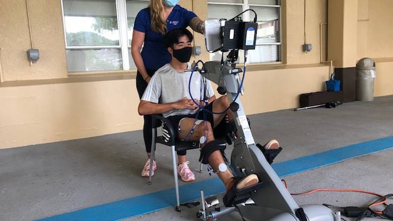 Under the watchful of physical therapist Leigha Stafford, 17-year-old David Togami rides a...