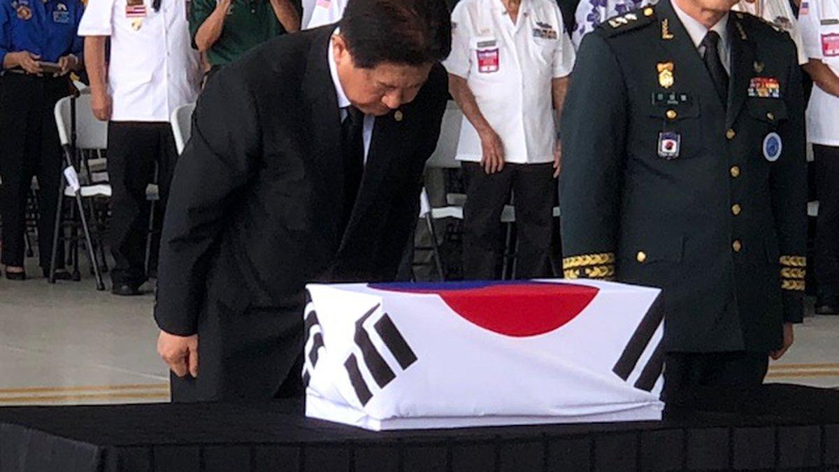 Choo Suk Suh, South Korea's Vice Minister of National Defense, bows before a box holding...