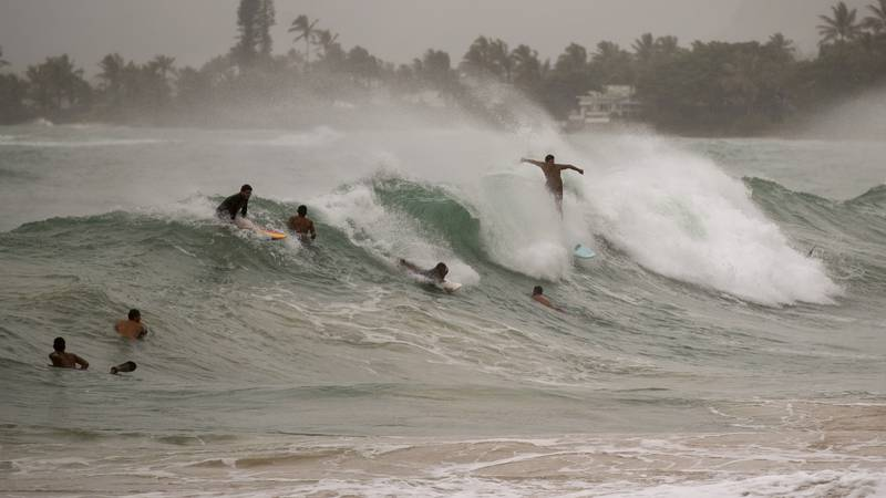 Surfers take on large waves generated by Hurricane Douglas at Laie Beach Park, Sunday, July 26,...