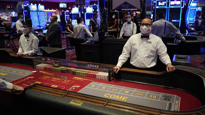 Dealers in masks wait for customers before the reopening of the D Las Vegas hotel and casino,...