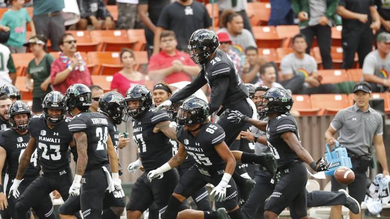 The Hawaii bench celebrates after Hawaii defensive back Kai Kaneshiro (24) intercepted an...