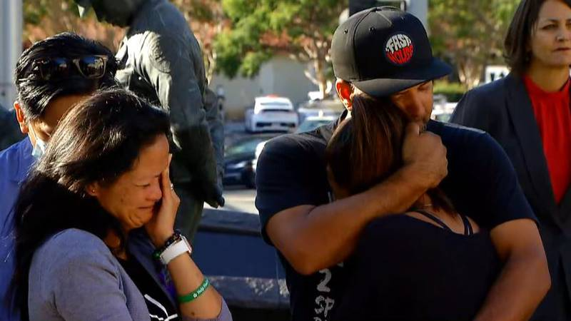 Emotional family members embrace Wednesday following a news conference announcing the arrest of...
