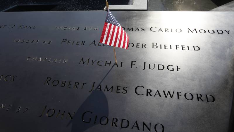 FILE - In this Monday, Sept. 12, 2011 file photo, a U.S. flag is stuck into the etched name of...