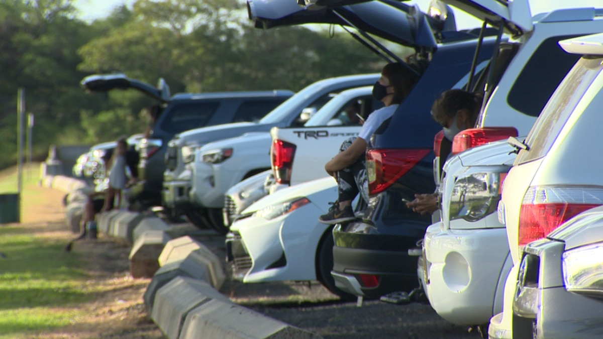 Soccer parents watch from their parked vehicles while their kids practice.
