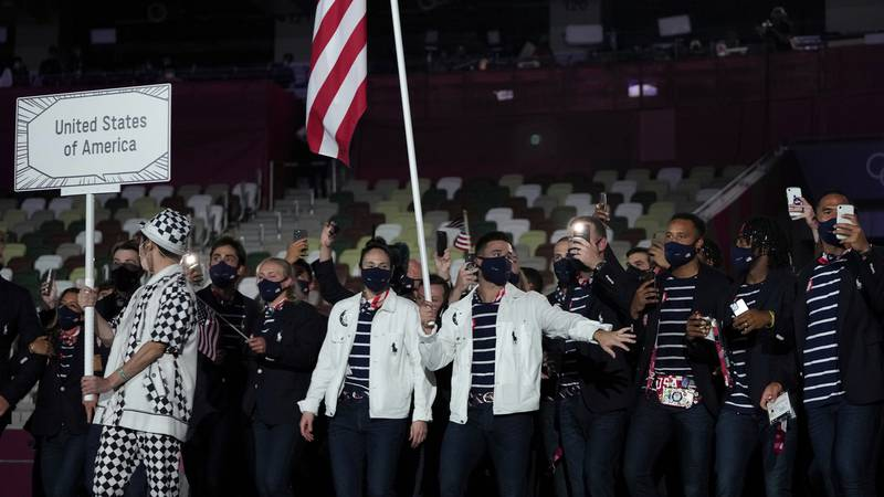Sue Bird and Eddy Alvares, of the United States of America, carry their country's flag during...