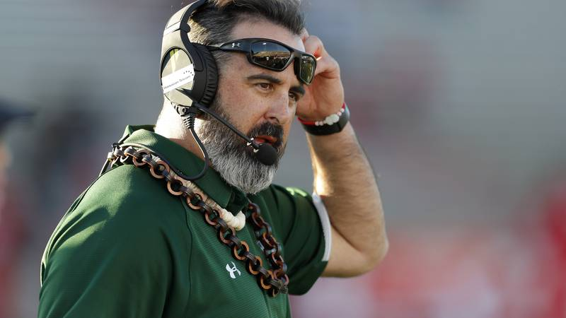 Hawaii coach Nick Rolovich speaks through his headset during a timeout in the second half of an...