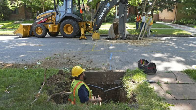 A Denver Water crew works to replace a lead water service line installed in 1927 with a new...