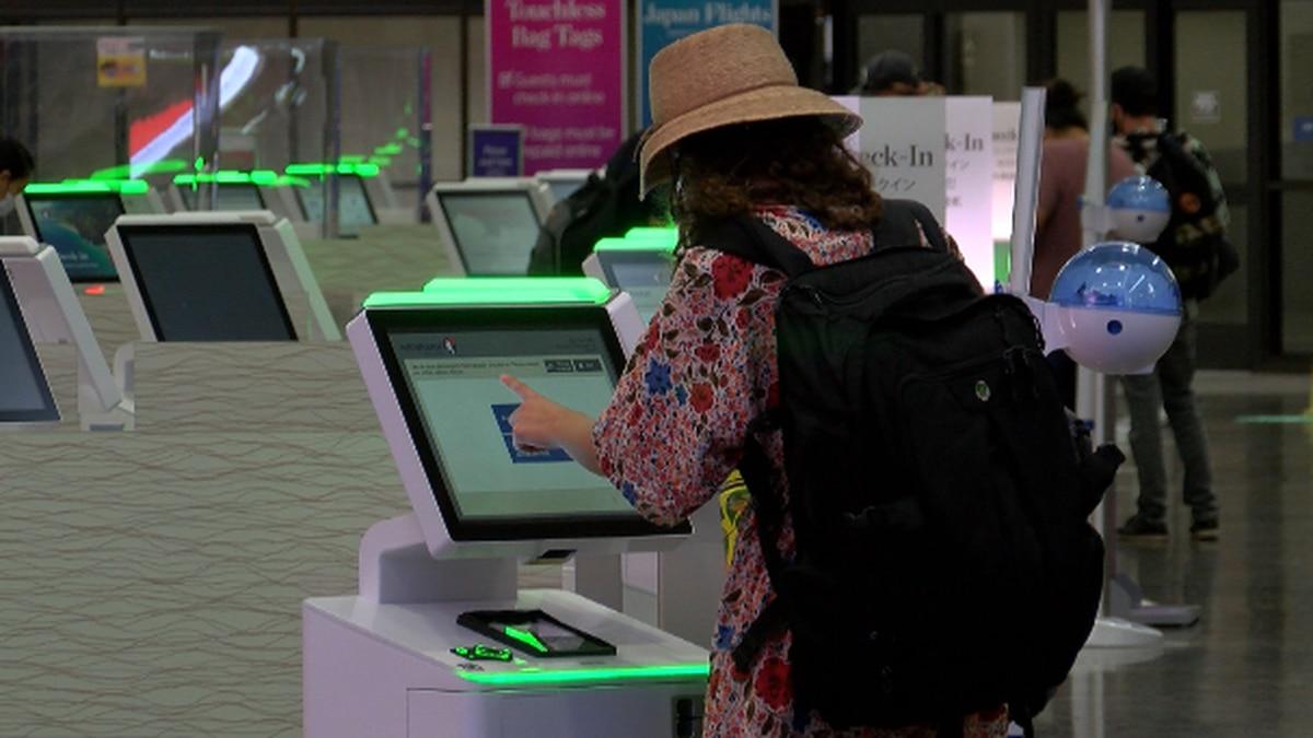 Traveler checks into flight at Hawaiian Airlines terminal.