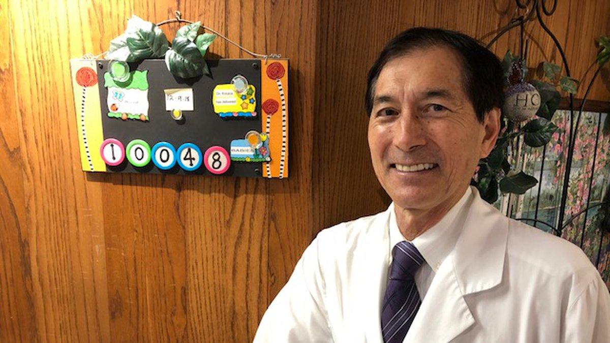 Kapiolani Medical Center obstetrician and gynecologist Thomas Kosasa poses next to the board...