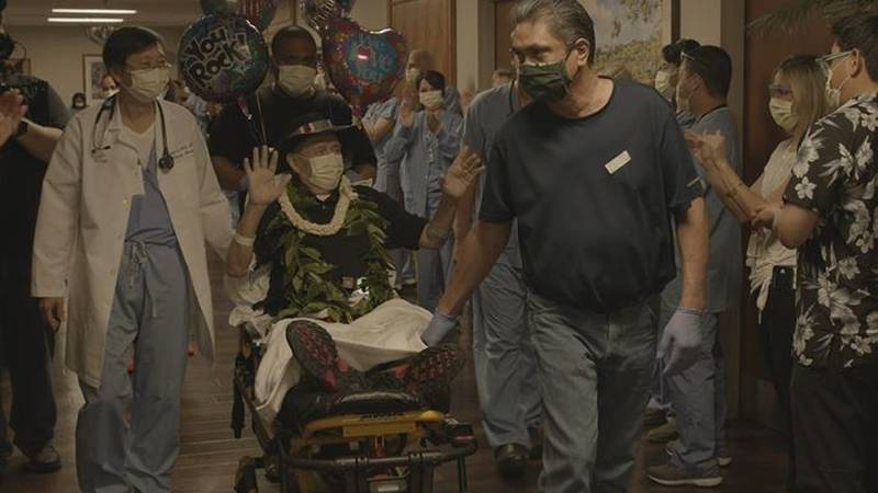 Wearing maile, pikake, and his signature black hat, Jack Denis waved to the hospital staff who...