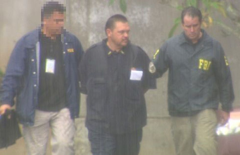 Adult Corrections Officer Mark Damas, flanked by arresting offers, after his arrest at Halawa...