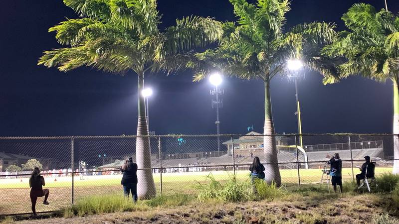 Fans kept away from the stands watch the OIA season football opener for Kapolei and Kahuku.