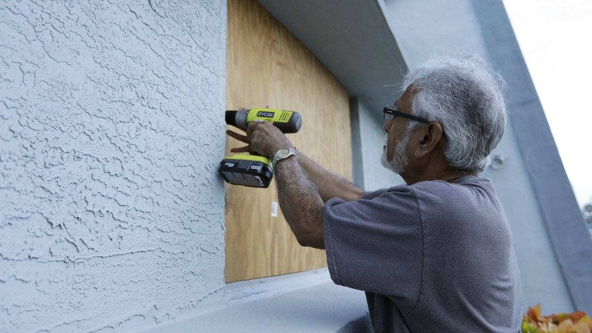 Ray Gohill, owner of the Sahara Motel, does some last minute boarding up of his windows...