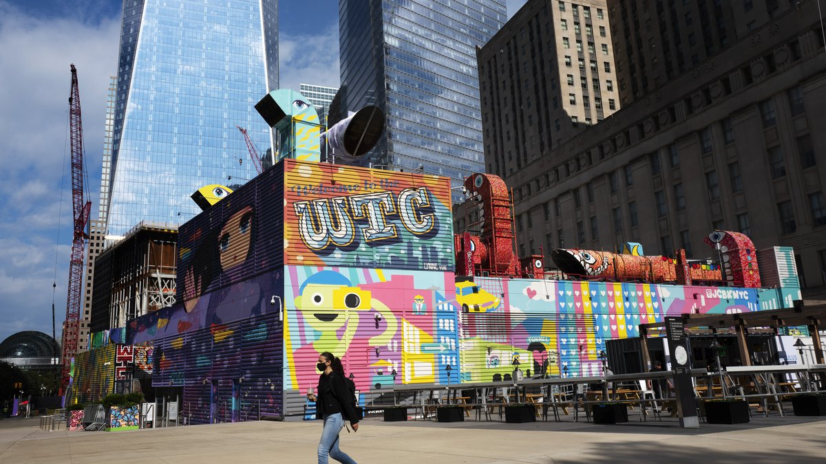 A woman walks by the colorful murals that surround the foundation for 2 World Trade Center,...