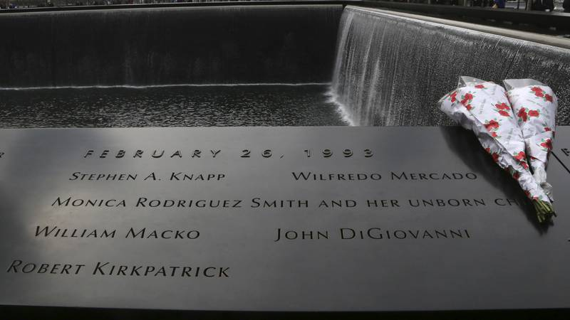 Flowers are placed near the names of the six people who were killed 20 years ago in the first...