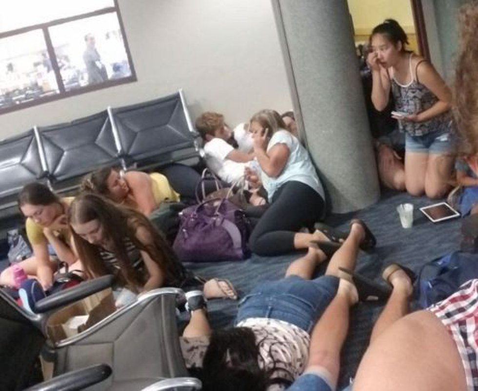Passengers huddled on the floor during a false security scare at Honolulu's airport. (Image:...