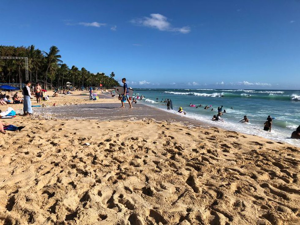 Beach-goers see the effects of the king tides on Waikiki Beach as the water flows onto the sand.