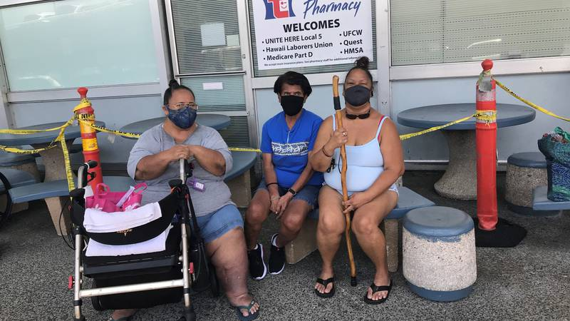 Three friends who have gotten vaccinated or plan to sit outside Times Pharmacy at the...