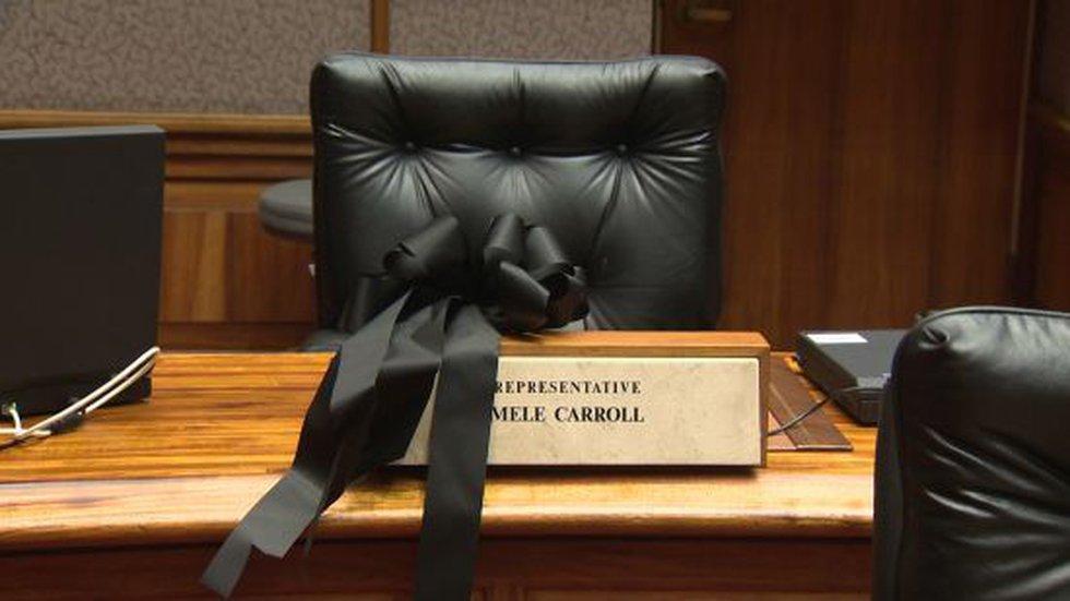 A black ribbon is shown on Rep. Mele Carroll's empty desk