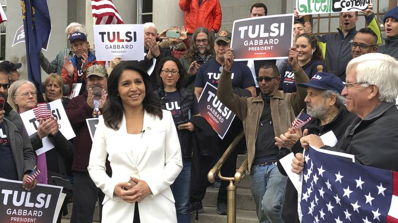 U.S. Rep. Tulsi Gabbard, of Hawaii, center, addresses a crowd outside the New Hampshire...