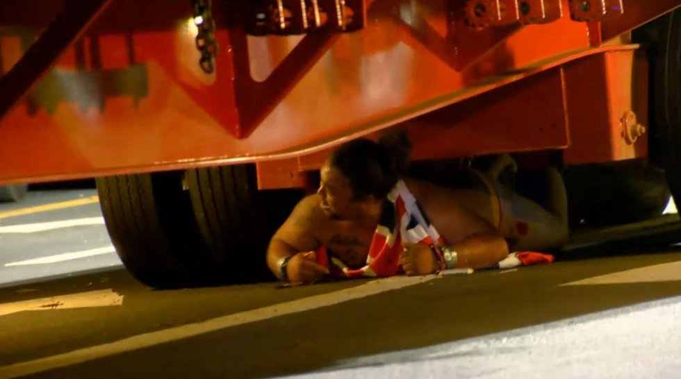 Henderson wedges himself under a semi-truck during the protest. (Image: Hawaii News Now)
