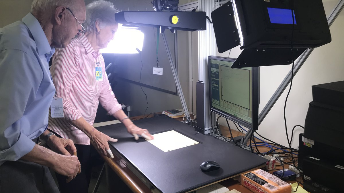 Volunteers David and Phyllis Walch photograph tax records.