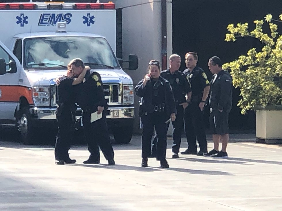 Honolulu police officers can be seen consoling each other outside the Queen's Medical Center.
