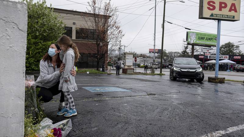 Mallory Rahman and her daughter Zara Rahman, 4, who live nearby, pause after bringing flowers...