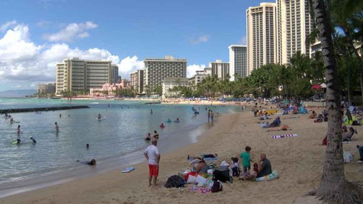 Visitors lounge on Waikiki on a Tuesday afternoon. There's growing concern about how the...