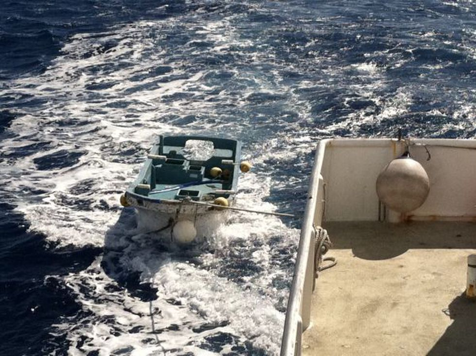 The skiff being towed to Hawaii after cleaning