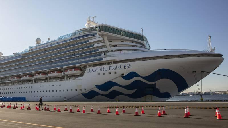 A reporter walks near the quarantined Diamond Princess cruise ship in Yokohama, near Tokyo,...