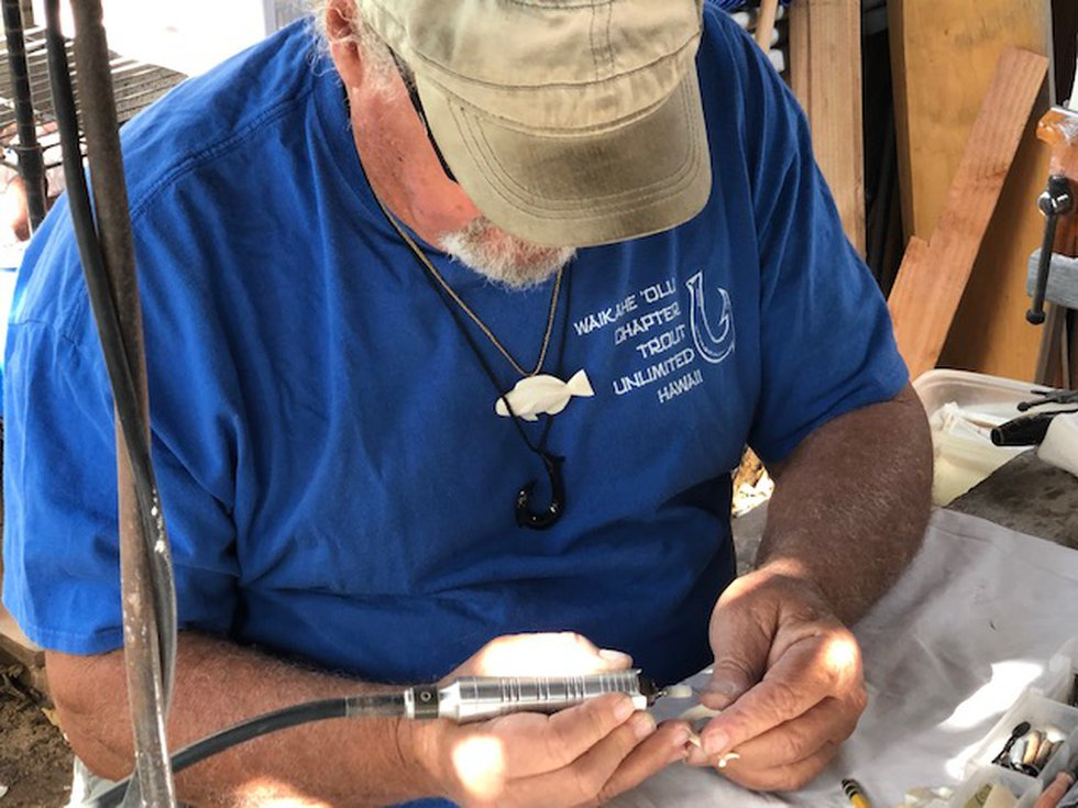 DeNolfo works on a replica Hawaiian fish hook. He carved it out of cow bone he bought at Petco.