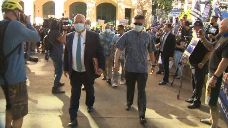 The 3 officers walk into court Friday morning through a crowd of HPD supporters.