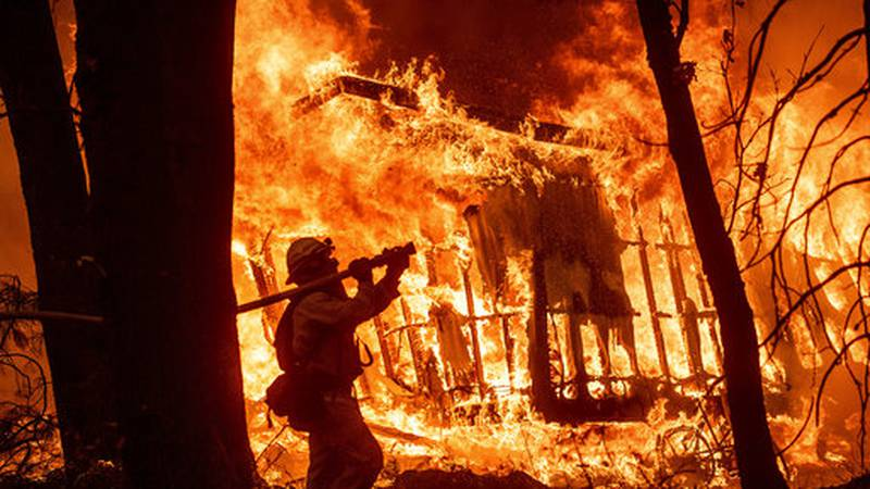 Firefighter Jose Corona sprays water as flames consume from the Camp Fire consume a home in...