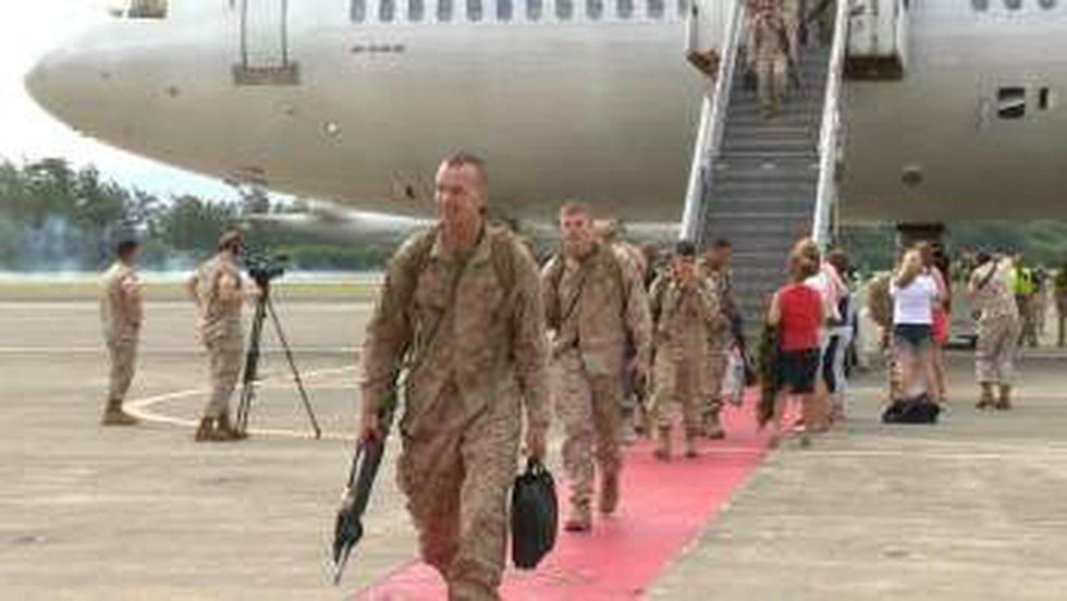 The first set of Marines and soldiers step off the plane.