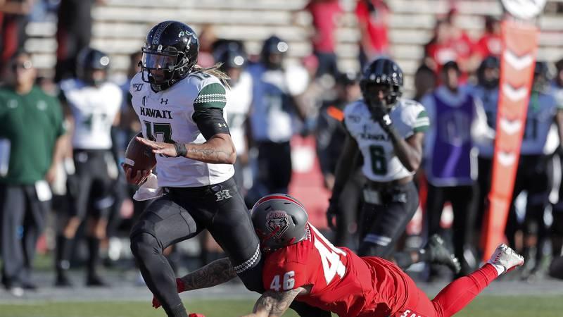 Hawaii quarterback Cole McDonald (13) is tackled by New Mexico linebacker Brandon Shook (46)...