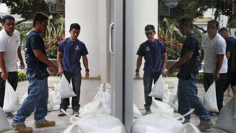 Workers stack sandbags in front of a closed store in preparation for Hurricane Lane, Thursday,...
