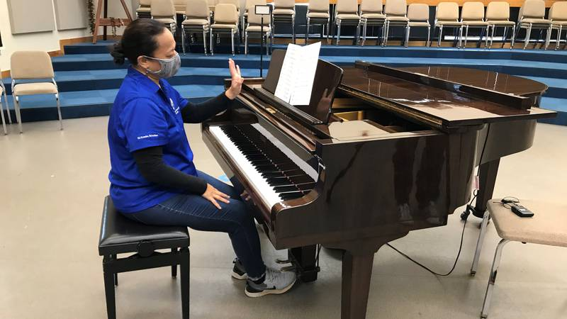 Kalua Leong, high school assistant choral director, plays a song that will be performed at Song...