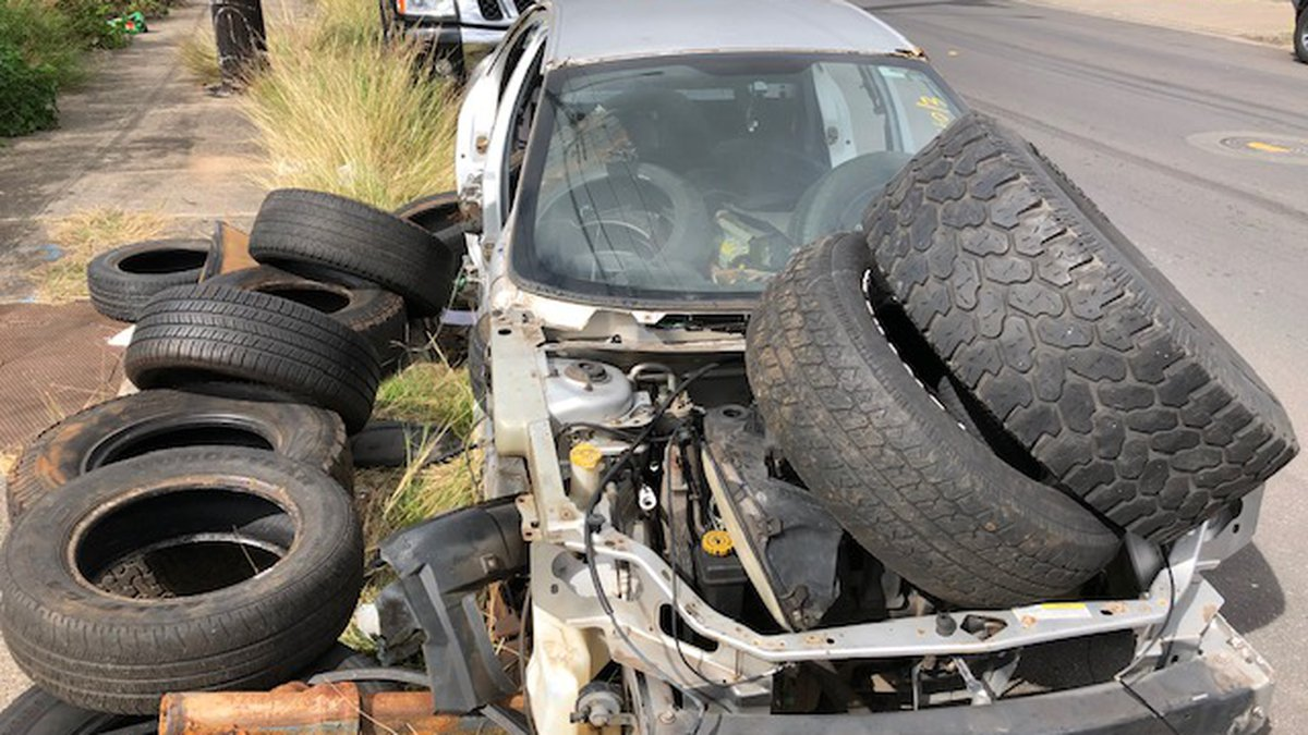 A car someone abandoned on Auiki Street in Kalihi has become a dump site for discarded tires.